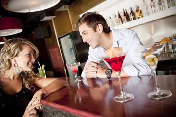 Hispanic woman drinking cocktail talking to bartender