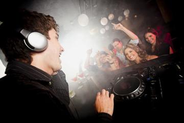 DJ playing music for crowd in nightclub