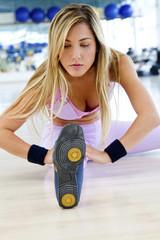 Hispanic woman stretching in health club