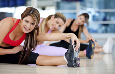 Hispanic women stretching in health club