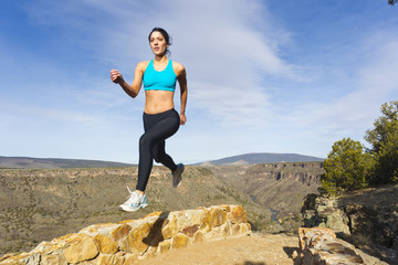 Hispanic woman jumping in mid-air in remote area