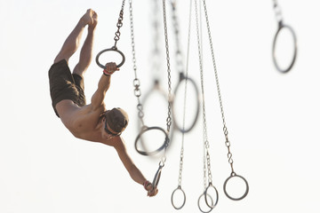 Mixed race man swinging on athletic rings
