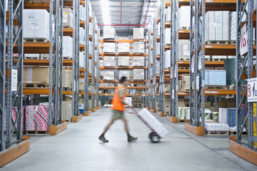Worker pushing hand truck in warehouse