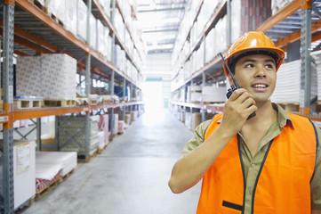 Worker talking on walkie talkie in warehouse