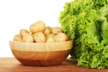 young potatoes in a wooden bowl with lettuce