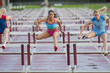Runners jumping hurdles in race