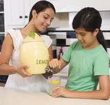 Hispanic mother and daughter pouring lemonade