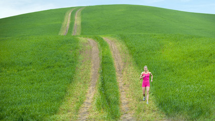 Caucasian woman running on path through field