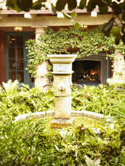 Water fountain and fireplace in lush courtyard