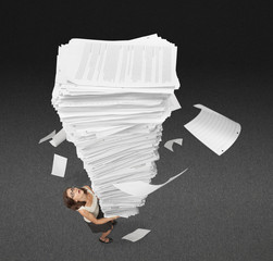 Mixed race businesswoman carrying large stack of papers