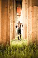 African American man jogging between pillars
