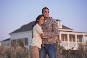 Hispanic couple hugging near beach house