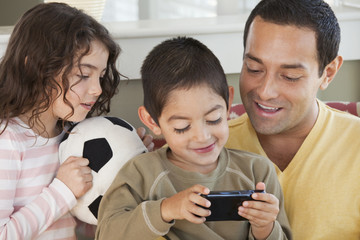 Father and sister watching boy play video game