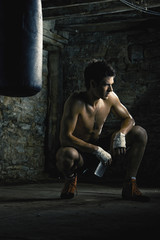 Caucasian boxer drinking water after training