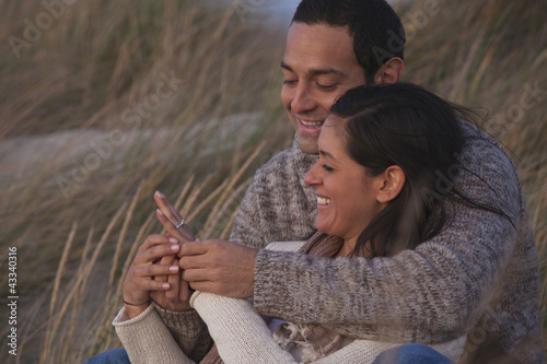 Hispanic couple looking at engagement ring