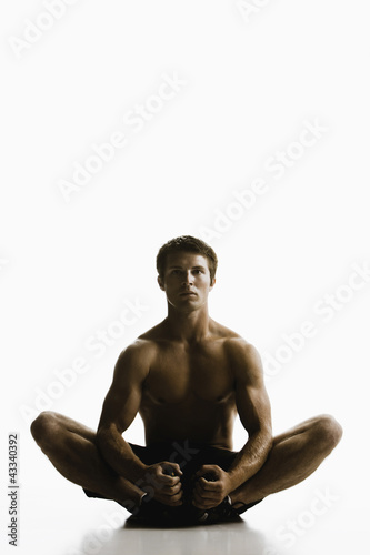 Caucasian man sitting on floor stretching