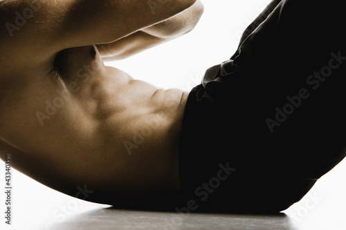 Caucasian man doing sit-ups