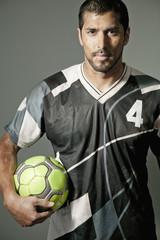 Serious athlete holding soccer ball
