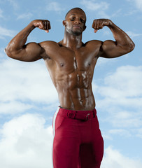 Black football player flexing muscles