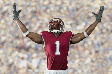 Black football player standing with arms raised