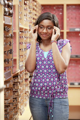 African American girl trying on eyeglasses in store