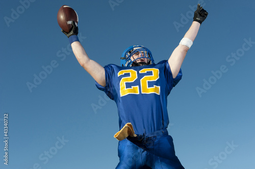 Caucasian football player holding football with arms raised