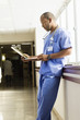 Black doctor looking at medical chart in hospital