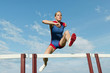 Caucasian runner jumping over hurdles on track