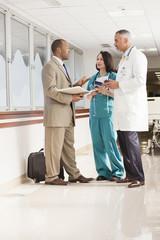 Doctors and drug salesman talking in hospital