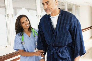 Nurse helping patient walk in hospital