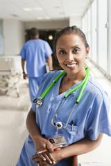 Smiling nurse leaning on window sill in hospital