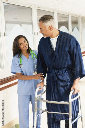 Nurse helping patient use walker in hospital