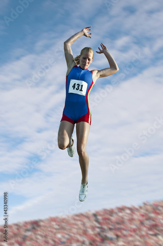 Caucasian athlete jumping in the long jump