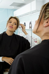 Hispanic woman looking at reflection in beauty salon