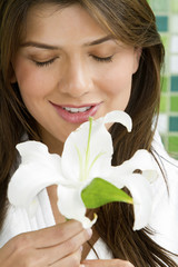 Hispanic woman smelling exotic flower