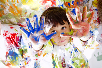 Messy Hispanic boy finger painting