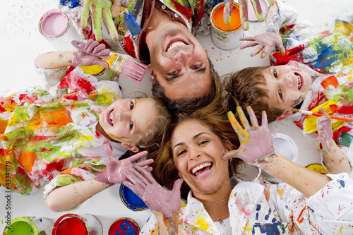 Hispanic family covered in paint laying on floor