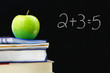 Addition equation written on a blackboard, books and apple