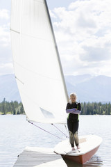 Girl standing on sailboat moored at dock