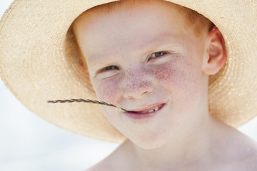 Freckled boy in hat chewing on straw