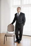 Mixed race businessman standing near chair