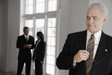 Businessman listening to co-workers in background
