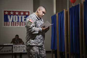 Hispanic soldier waiting to vote in polling place
