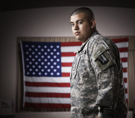 Hispanic soldier standing in front of American flag