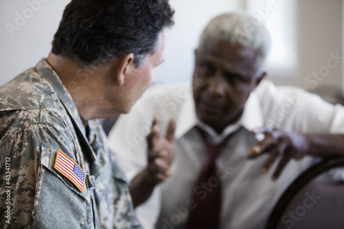 Soldier sitting in chair talking to businessman