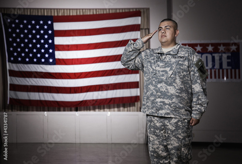 Hispanic soldier saluting American flag
