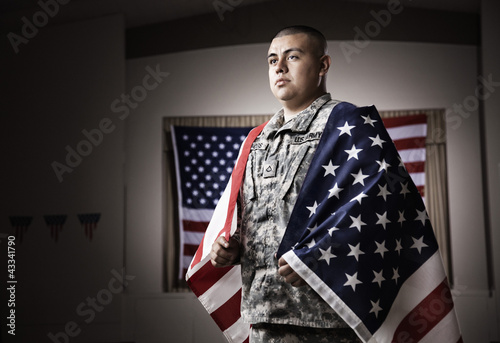 Hispanic soldier wrapped in American flag