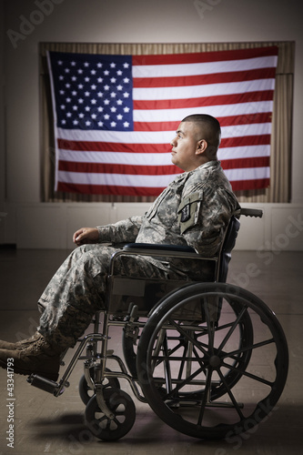 Hispanic soldier in wheelchair near American flag