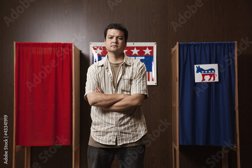 Mixed race man waiting to vote in polling place