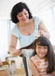 Hispanic woman brushing daughter's hair